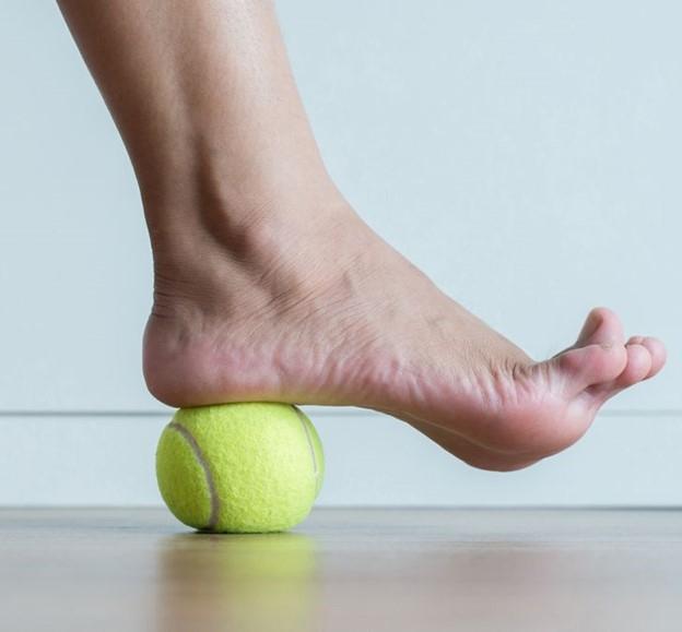 Xoa bóp bàn chân bằng một quả bóng tennis